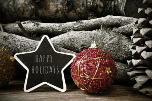 a star-shaped chalkboard with the text happy holidays surrounded by christmas balls and natural ornaments such as pine cones